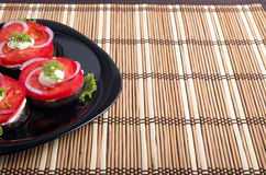 Black dish with sliced tomatoes and lettuce decorated with onion Stock Photos