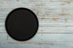 Black dish on a woody white blue background. A mockup of black woody delicate white blue background. View from above. Black dish on a woody white blue royalty free stock images