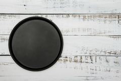 Black dish on a woody white blue background. A mockup of black woody delicate white blue background. View from above. Black dish on a woody white blue stock photos