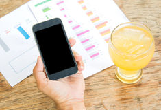 Black display Smart phone in hand , Cold glass lemonade  , Graph. Data analysis placed on wooden floor Royalty Free Stock Images