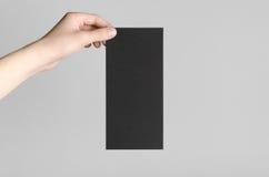 Black DL Flyer Mock-Up. Male hands holding black flyers on a gray background Stock Image