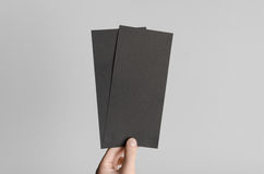 Black DL Flyer Mock-Up. Male hands holding black flyers on a gray background Royalty Free Stock Image