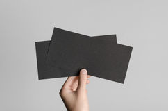 Black DL Flyer Mock-Up. Male hands holding black flyers on a gray background Royalty Free Stock Images