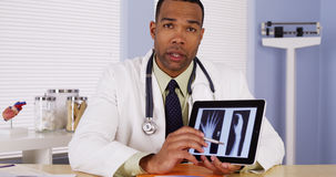 Black doctor listening and talking to camera Stock Image