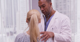 Black doctor listening to patient's heart Stock Photography