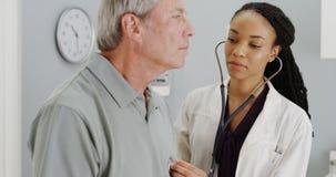 Black doctor listening to senior breathing Stock Image