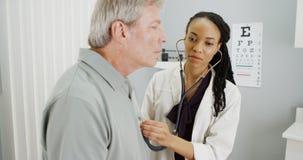 Black doctor listening to senior breathing Royalty Free Stock Image