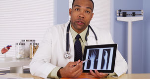 Black doctor reviewing wrist x-ray Stock Photo