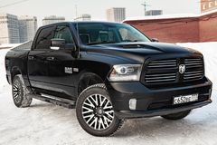 Black Dodge Ram with an engine of 5.7 liters front view on the car parking with snow background royalty free stock images