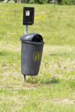 Black dog litter bin on lawn Stock Photography