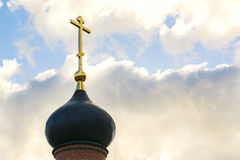 Black dome of the Church with a golden cross on the sky background with white clouds. tower of the old red brick in the light of t Stock Photos