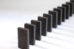 Black dominoes. In a row casting a shadow on white royalty free stock images