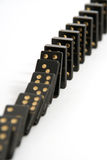 Black Dominoes Falling Down in a Line. A line of black dominoes falling down, isolated on a white background with a narrow depth of field stock image