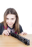 Black Dominoes In A Row And Cute Girl Looking At Camera Isolated On White Stock Photo
