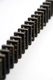 Black Dominoes Standing in Line. A line of black and gold dominoes standing in line on a white background. Narrow depth of field Royalty Free Stock Photography