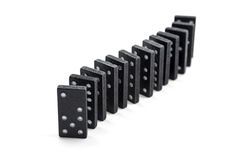 Black dominos in a row isolated on a white background. Black dominoes in a row isolated on a white background, selective focus and narrow depth of field Royalty Free Stock Photo