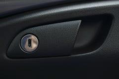 Black door handle of car interior with lock Stock Photo