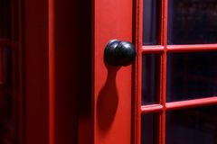 Black door handle on the English phone booth royalty free stock images