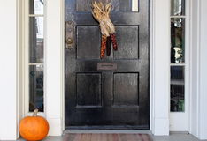 Black door with indian corn and fall pumpkin Stock Photography