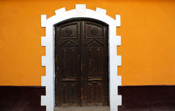 Black door, Yellow Wall. On a colonial style building in Puno, Peru royalty free stock photos