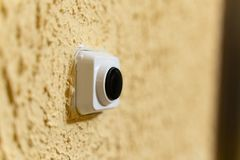 Black doorbell button in white case on yellow wall with embossed texture royalty free stock photos