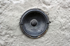 Black doorbell in white wall. Close-up of a vintage doorbell in a white plastered old wall Stock Photo