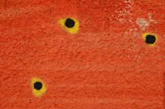 Black dots on orange. Three black and yellow dots painted on textured concrete wall sprayed with orange graffiti paint Stock Image