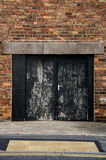 Black double backdoor. In old brick building stock image