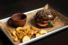 Black double hamburger made from beef, cheese and vegetables. Stock Images