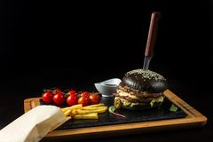Black double hamburger made from beef with jalapeno pepper, cheese and vegetables-4 Stock Images