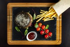 Black double hamburger made from beef with jalapeno pepper, cheese and vegetables. Top view. Royalty Free Stock Photos