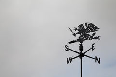 Black dragon wind vane against the sky. Weather vane. Compass points Stock Image