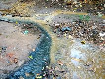 Black drain water and yellow muddy soil water flowing. Black drain water and yellow muddy soil water mix at an India rural village wet path street and flowing royalty free stock image