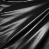 Black drape. Wavy folds of synthetic material. Royalty Free Stock Photos