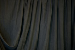 Black Draped Background. A black draped backdrop cloth fills the image with vertical folds Stock Image