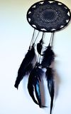 Black dreamcatcher hanging on a wall. Black dreamcatcher hanging on a white wall with black feathers on it Stock Photos