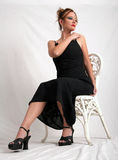 The black dress. Woman posing in black dress, sitting on white wicker chair Stock Images