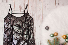 Black dress in a blaze on a wooden background, Christmas balls on white fur. Fashionable concept Royalty Free Stock Image