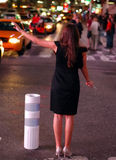Black Dress Hails a Cab. Young woman is black dress haling a cab. It is night time in Times Square royalty free stock images