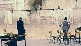Black dress Jewish man. Jerusalem, Israel - Circa 1981: Jewish man in typical black dress and hat washing his hands at Western Wall Plaza square in Old City of stock footage