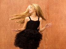 Black dress kid girl dancing and twisting vintage. Black dress kid girl dancing and twisting on vintage background Royalty Free Stock Images