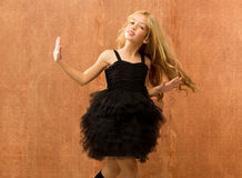 Black dress kid girl dancing and twisting vintage. Black dress kid girl dancing and twisting on vintage background Royalty Free Stock Photo