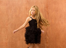 Black dress kid girl dancing and twisting vintage. Black dress kid girl dancing and twisting on vintage background Stock Photo