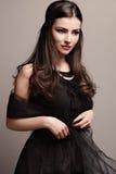Black dress and pearls. Stylish elegant woman in black dress wearing pearls, studio shot Royalty Free Stock Photography