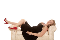 Black dress red shoes lay back couch Royalty Free Stock Photos