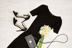 Black dress, shoes, clutch and a bouquet of daffodils. Fashionable concept. Wooden background Royalty Free Stock Photography
