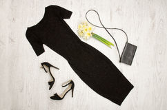 Black dress, shoes, clutch and a bouquet of daffodils. Fashionable concept. Wooden background Stock Images