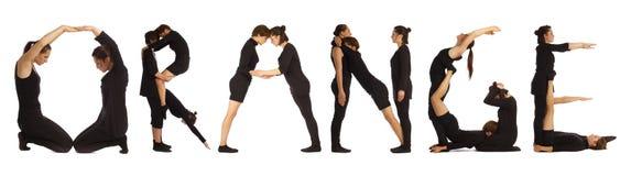 Black dressed people forming word ORANGE Stock Images