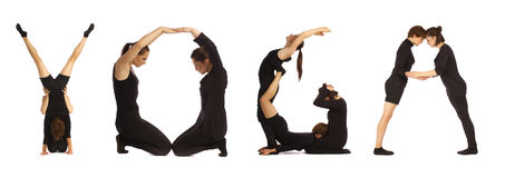 Black dressed people forming YOGA word over white. Background Royalty Free Stock Images