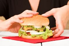 Black dressed woman holding a hamburger. Woman holding home made hamburger Royalty Free Stock Image